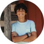 Smiling boy leaning against pole